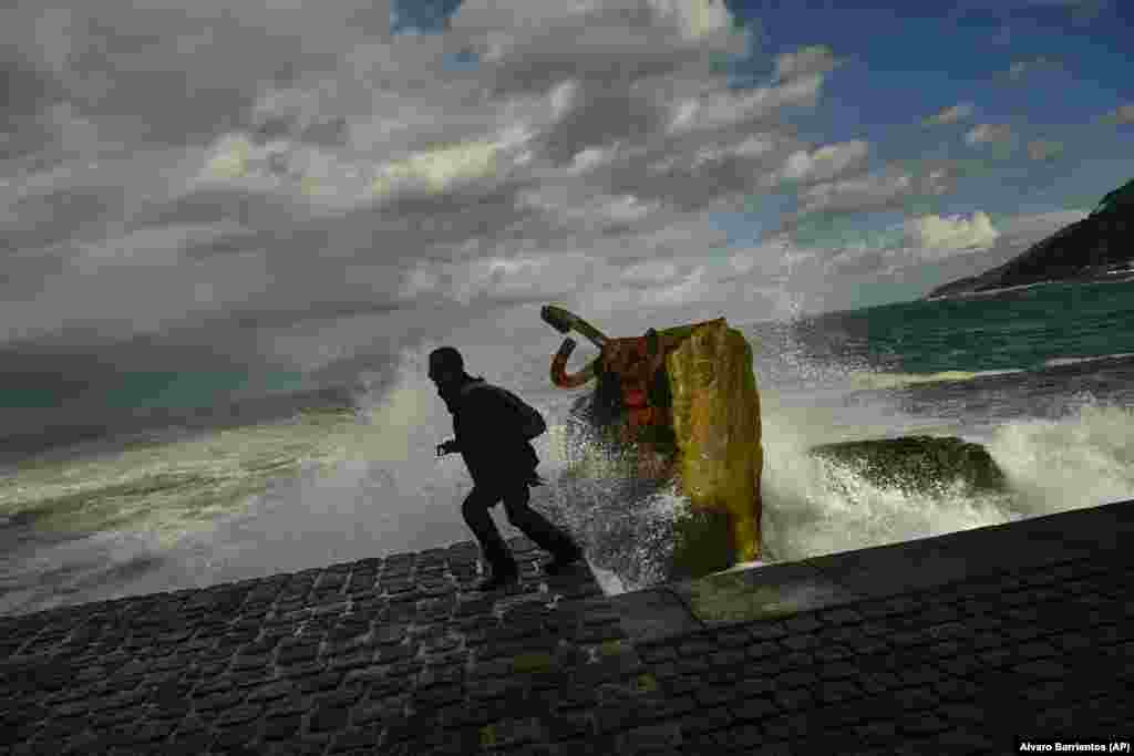 A man runs as a giant wave crashes against the sea defenses during high tide in San Sebastian, Spain. (AP/Alvaro Barrientos)