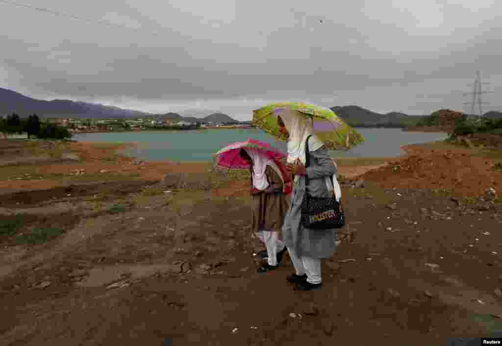 Afghan schoolgirls hold umbrellas to shelter from the rain on the outskirts of Kabul. (Reuters/Mohammad Ismail)