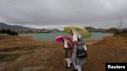 Afghan school girls hold umbrellas to shelter from rain on outskirt of Kabul on May 15.