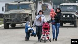 Жінки на прогулянці з дітьми поряд з українською військовою базою в селі Перевальне, 12 березня 2014 року
