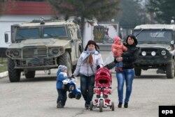 Женщины с детьми идут по улице, где стоят военные машины. Симферополь, 12 марта 2014 года.