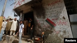 Men stand outside the campaign offices of the Muttahida Qaumi Movement (MQM) political party in Karachi on April 26, after a bomb blast.