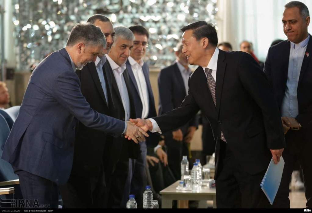 نماینده چین در نمایشگاه کتاب با وزیر ارشاد (چپ) دست میدهد.