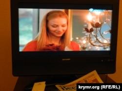 Передача российского ТВ на экране телевизора в Риге и латвийская газета на русском языке