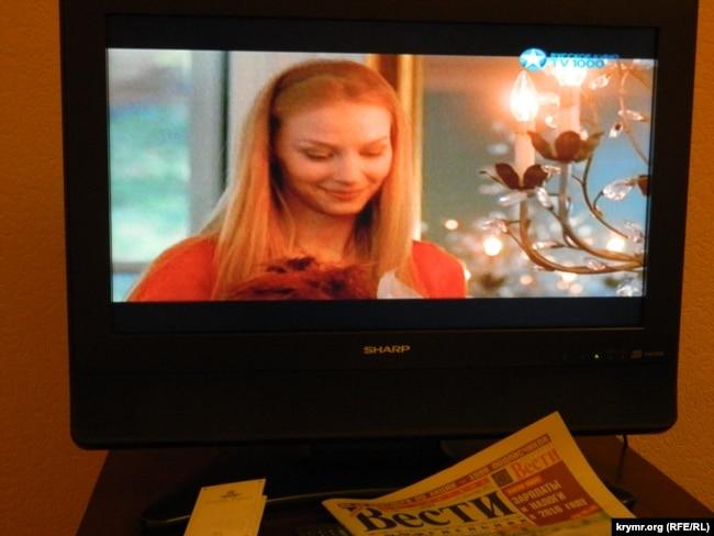 Передача российского ТВ на экране телевизора в Риге и продающаяся в Латвии российская газета