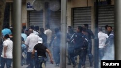 Protesters run for cover during riots in central Tunis on May 8