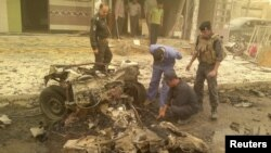 Iraqi security personnel inspect the site of a car bomb attack in the city of Ramadi on 19 April.