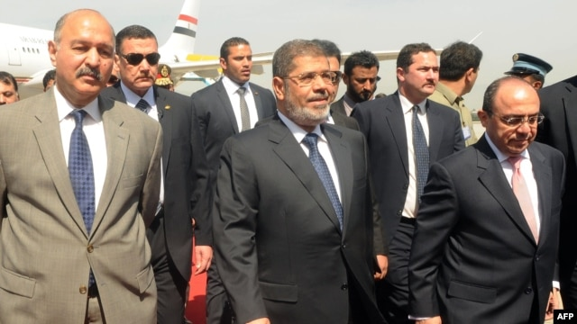 Egyptian President Muhammad Morsi (center) is flanked by Pakistani and Egyptian officials upon his arrival at the Chaklala military air base in Rawalpindi on March 18.
