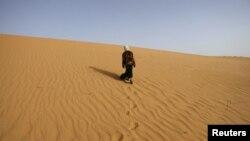 Сахара шөлінде кетіп бара жатқан әйел. Алжир, 24 наурыз 2008 жыл. (Көрнекі сурет)