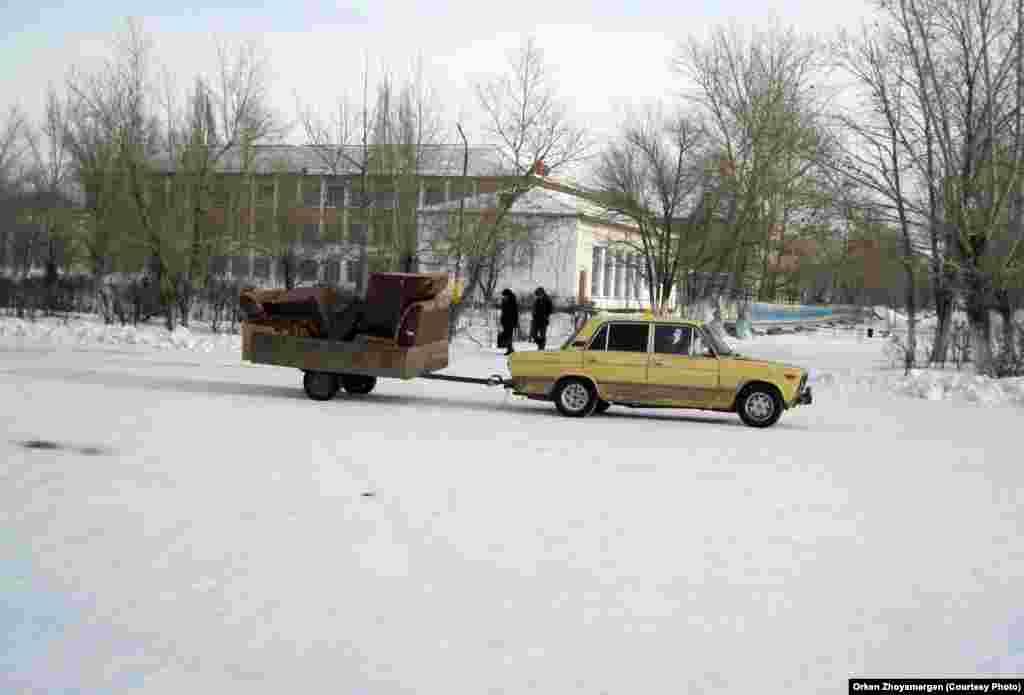 Машина, везущая на прицепе груз.