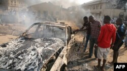 Men look at the wreckage of a car following a bomb blast at a church outside the Nigerian capital, Abuja, on December 25.