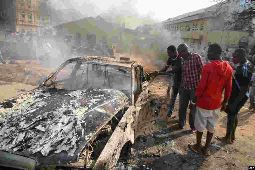 Men look at the wreckage of a car following a bomb blast at St Theresa's Catholic Church outside the Nigerian capital Abuja on Christmas Day. A radical Islamist group claimed responsibility for the attack. (AFP/Sunday Aghaeze)