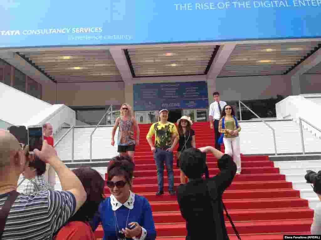 Туристы фотографируются на красной дорожке