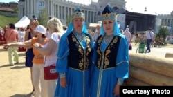 Женщина в татарских национальных костюмах приветствуют туристов, приехавших на Универсиаду в Казань. 16 июля 2013 года.
