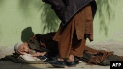 An elderly man lies on the ground as he begs in Kandahar. (file photo)