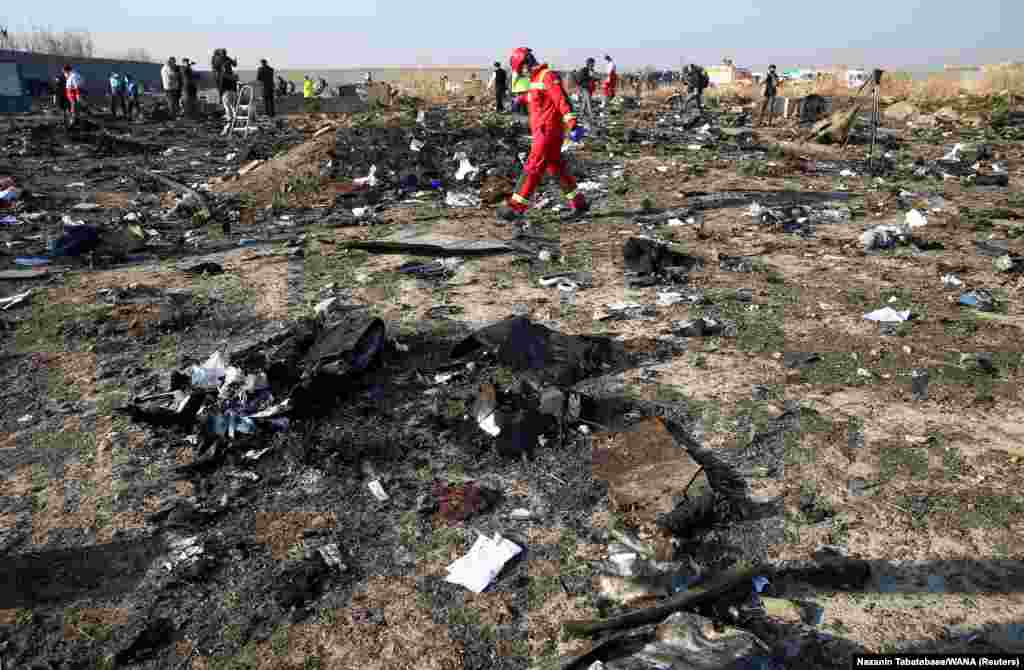 A member of a rescue team walks among debris from a plane belonging to Ukraine International Airlines, that crashed after a take-off from Iran's Imam Khomeini airport, on the outskirts of Tehran, Iran, January 8, 2020. (Nazanin Tabatabaee/WANA)