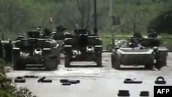 A video grab shows Syrian army tanks stationed in the Qusur district of the flashpoint city of Homs in early April.