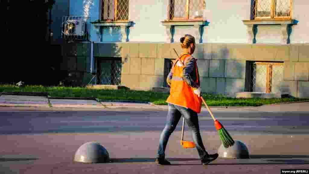Жінка-двірник наводить чистоту перед будівлею російського уряду Криму