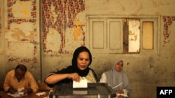 An Egyptian Christian Coptic woman casts her vote in the country's presidential election at a polling station in Cairo.