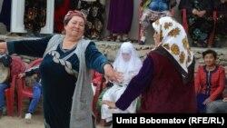Женщины танцуют в день свадьбы во дворе, где сидит невеста. Север Таджикистана, апрель 2015 года. Иллюстративное фото.