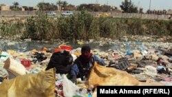 سيدة تبحث وسط أكوام النفايات عما يمكن إعادة تصنيعه