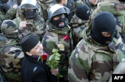 A Georgian woman holding flowers smiles as special forces leave without bloodshed outside the presidential residence of Eduard Shevardnadze on November 22, 2003.