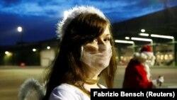 Një grua me një kostum engjëlli të Krishtlindjeve mban një maskë mbrojtëse për fytyrën gjatë një organizimi në Berlin, Gjermani.