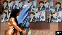 Women walk past posters of President Hamid Karzai in Kabul.