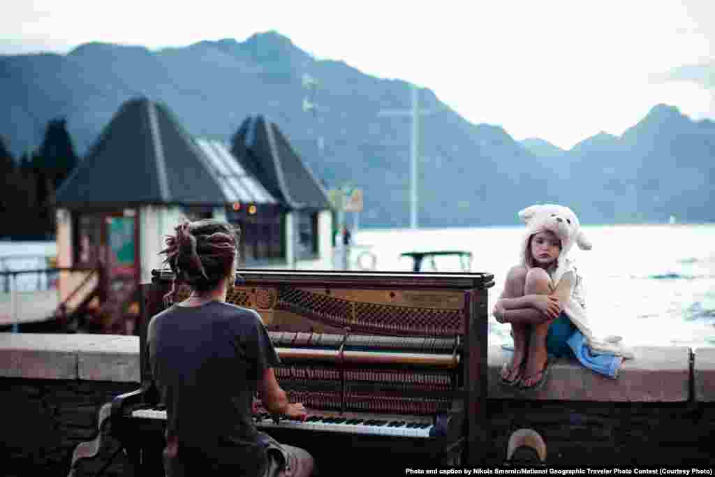 "Merit Award: ""Piano Play At Sunset"" by Nikola Smernic: ""Streets of Queenstown, New Zealand, at the end of one more day filled with adrenaline. Calming and doleful scene with piano sound in the background."""