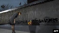 """Ukrayna prezidentinin xanımı Marina Poroshenko Vaşinqtonda """"Qolodomor"""" abidəsi önündə baş əyərkən"""