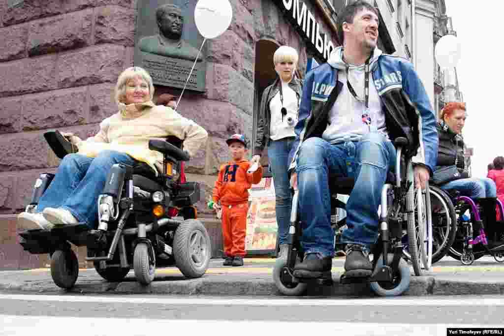 Артист Артур Смолянинов (справа) пытается выехать на пешеходный переход по специально заниженному для инвалидов бордюру.