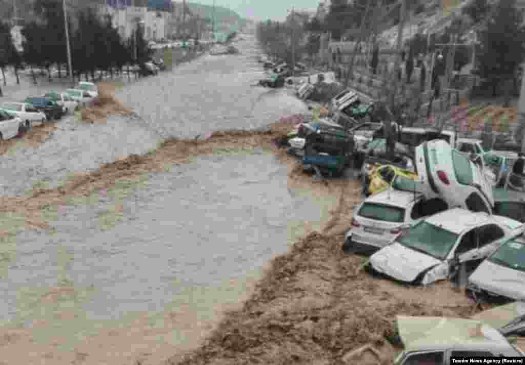 Vehicles are piled up after being swept away by flash floods in Shiraz.