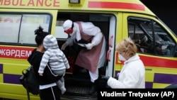 Медик в защитном костюме выходит из машины скорой помощи.
