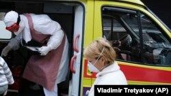 Медработники у автомобиля скорой помощи.