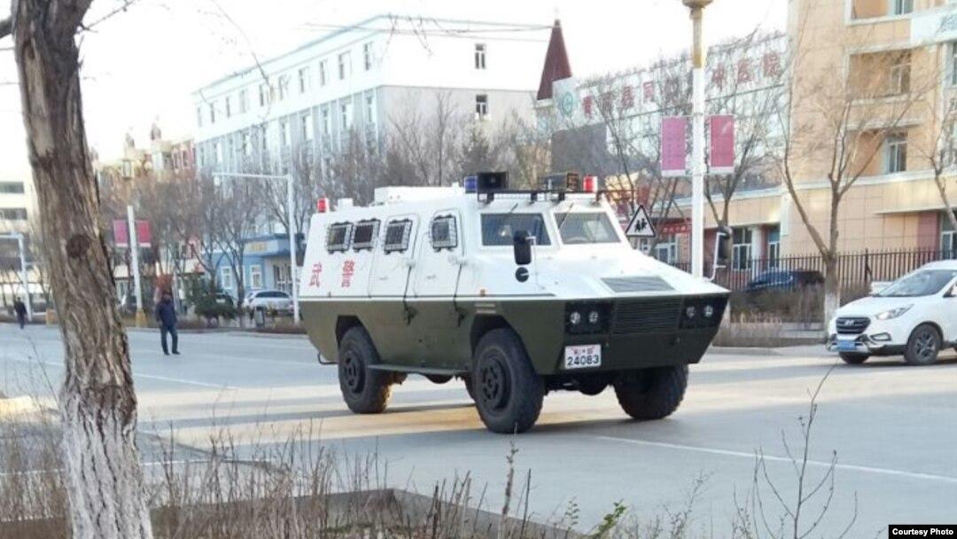 Военный автомобиль на улице населенного пункта в Синьцзяне.