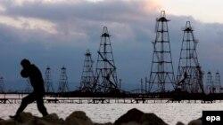 Рабочий на фоне нефтяных вышек на берегу Каспийского моря.