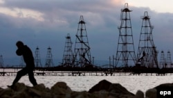 A man walks in front of oil derricks on the Caspian Sea near the Azerbaijani capital Baku.