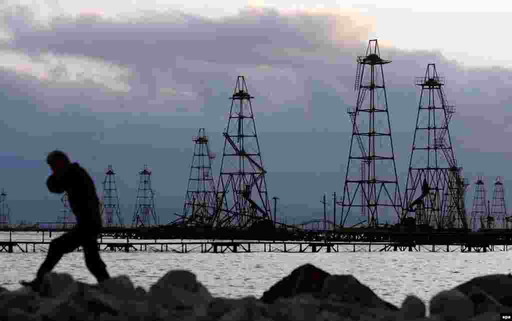 "A worker walks in front of the oil derricks on the Caspian Sea near Baku. With no end in sight to the economic crisis President Aliyev has made a plea for citizens to ""work more efficiently."" But patience on the street for the big-spending regime is wearing thin."