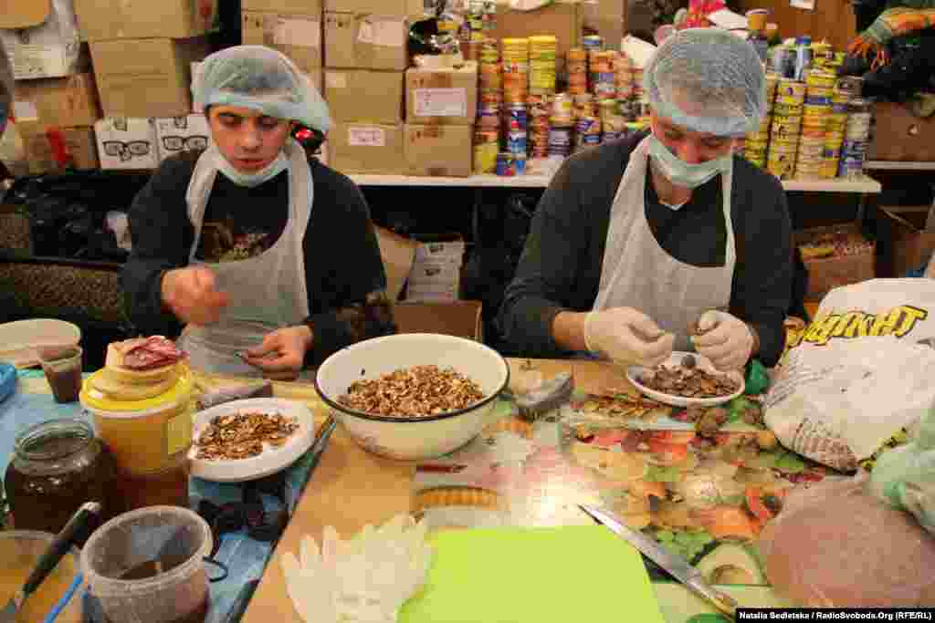 Volunteers in gloves and hairnets prepare food at the dining hall of a trade union building, the main kitchen offering food to the protesters.