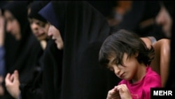 Iranian women and a young girl at a conservative meeting (file photo)