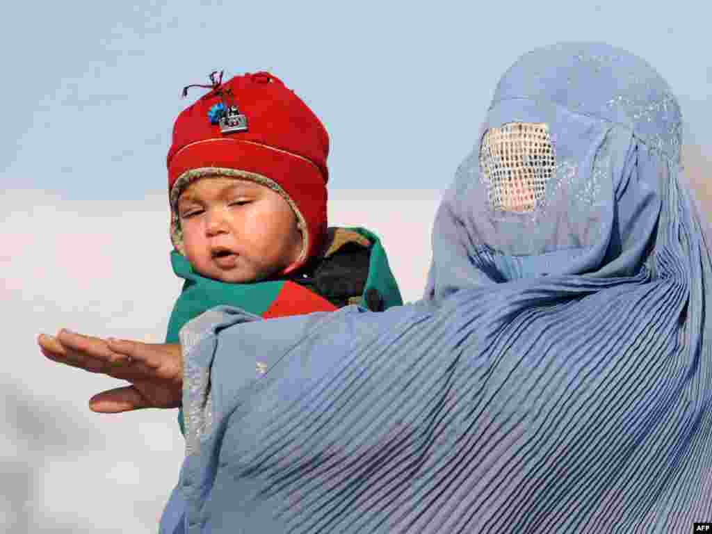 A burqa-clad Afghan woman holds her child as she stops a taxi on the outskirts of Kabul on February 14. Photo by Marai Shah for AFP