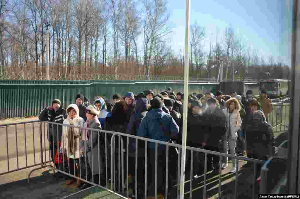 Люди стоят в очереди перед миграционным центром в Сахарово.