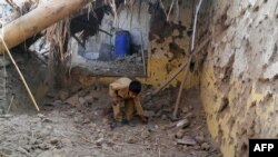 FILE: A child sifts through rubble at a destroyed religious seminary belonging to the Haqqani network after a U.S. drone strike in the Hangu district of Khyber Pakhtunkhwa province in November 21. The regions borders Kurram.