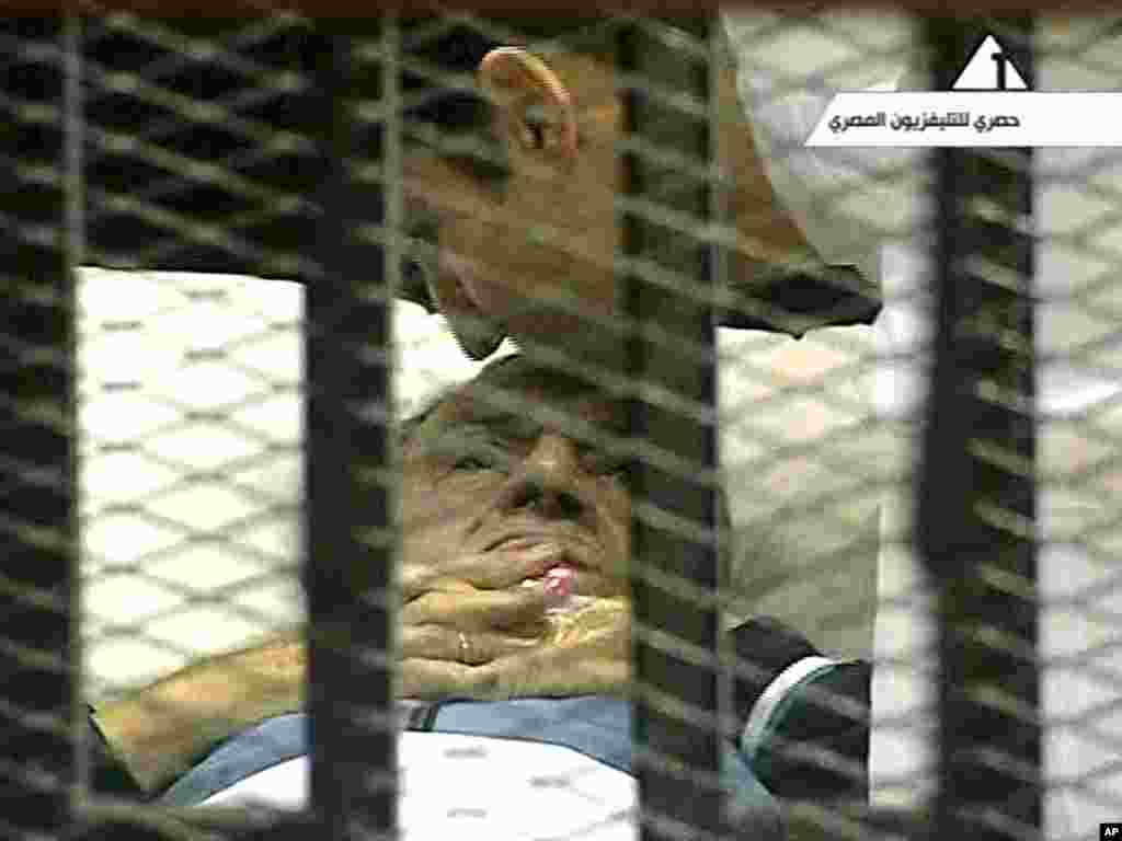 In this video image taken from Egyptian state television, 83-year-old former Egyptian President Hosni Mubarak is kissed by his son Alaa as he lies on a bed within a cage at the court building in Cairo. Mubarak returned to a Cairo court on a stretcher for another session of his trial on charges of corruption and complicity in killing protesters during Egypt's uprising.