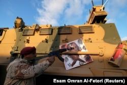 Боец Ливийской национальной армии Халифы Хафтара целится автоматом в портрет Реджепа Эрдогана на борту своего БТР. Город Сирт, июль 2020 года