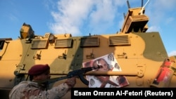 A member of Libyan National Army (LNA) commanded by Khalifa Haftar, points his gun at the image of Turkish President Recep Tayyip Erdogan on a Turkish military armored vehicle, which LNA said they confiscated during Tripoli clashes.