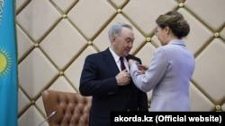 Спикер сената Казахстана Дарига Назарбаева вручает своему отцу экс-президенту Нурсултану Назарбаеву нагрудный знак «почетного сенатора». Нур-Султан, 6 июня 2019 года.