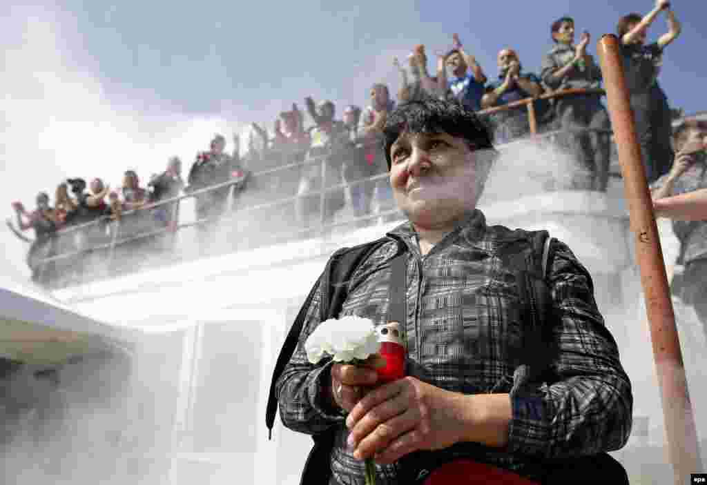 A Romanian woman holds flowers and a candle to pay tribute to Dinamo's Cameroonian midfielder Patrick Claude Ekeng during a ceremony at Dinamo Stadium in Bucharest. Ekeng collapsed during a Romanian Premier Soccer League playoff match between Dinamo Bucharest and Victoria in Bucharest on May 6. Ekeng fell unconscious without being touched by any other player and died at hospital hours later from a suspected heart attack. He was 26. (epa/Robert Ghement)
