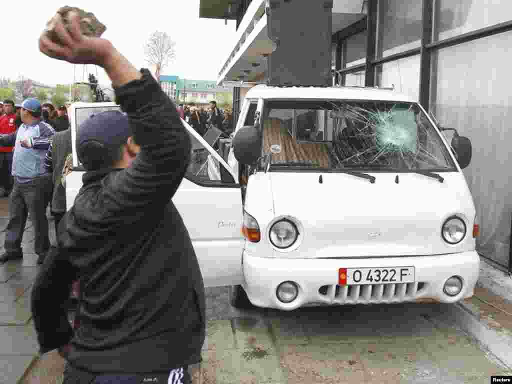 Сторонник Временного правительства бросает камень в автомобиль сторонников президента Бакиева. Ош, 15 апреля 2010 года.