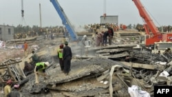 Pakistani rescuers search for victims in the rubble of a collapsed factory on the outskirts of Lahore on November 6.